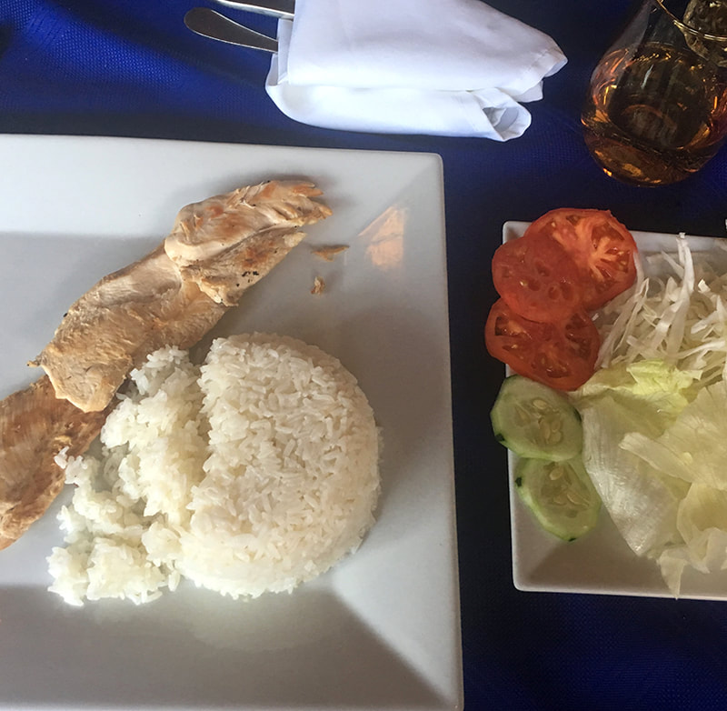 chicken and rice on a plate with a salad of lettuce, tomatoes and cucumbers on the side