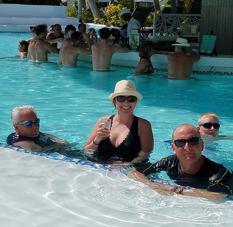 Shane and her husband, dad, and son in the pool with a swim up bar in the background