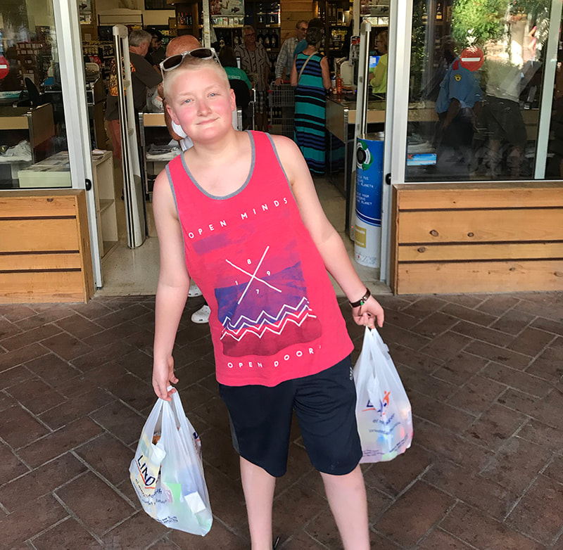 Teen boy carrying plastic bags of groceries out of the super market